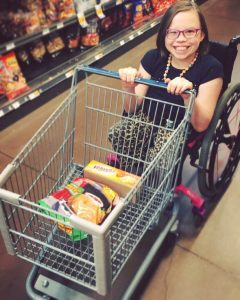 girl with CRS pushing shopping cart